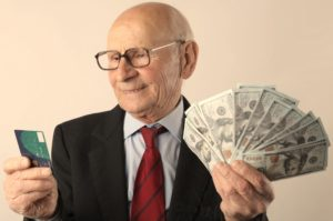 an older man holding a credit card on the right hand and cash on the left hand
